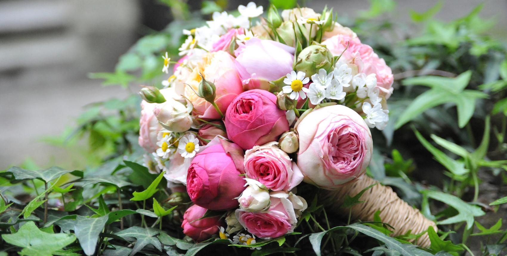 Hochzeitsfloristik Brautstrauss bestehend aus Pfingstrosen normalen Rosen in rosa Toenen und anderer kleiner weißen Blumen mit einer hellbraunen Schnur zusammengebunden in Efeu liegend
