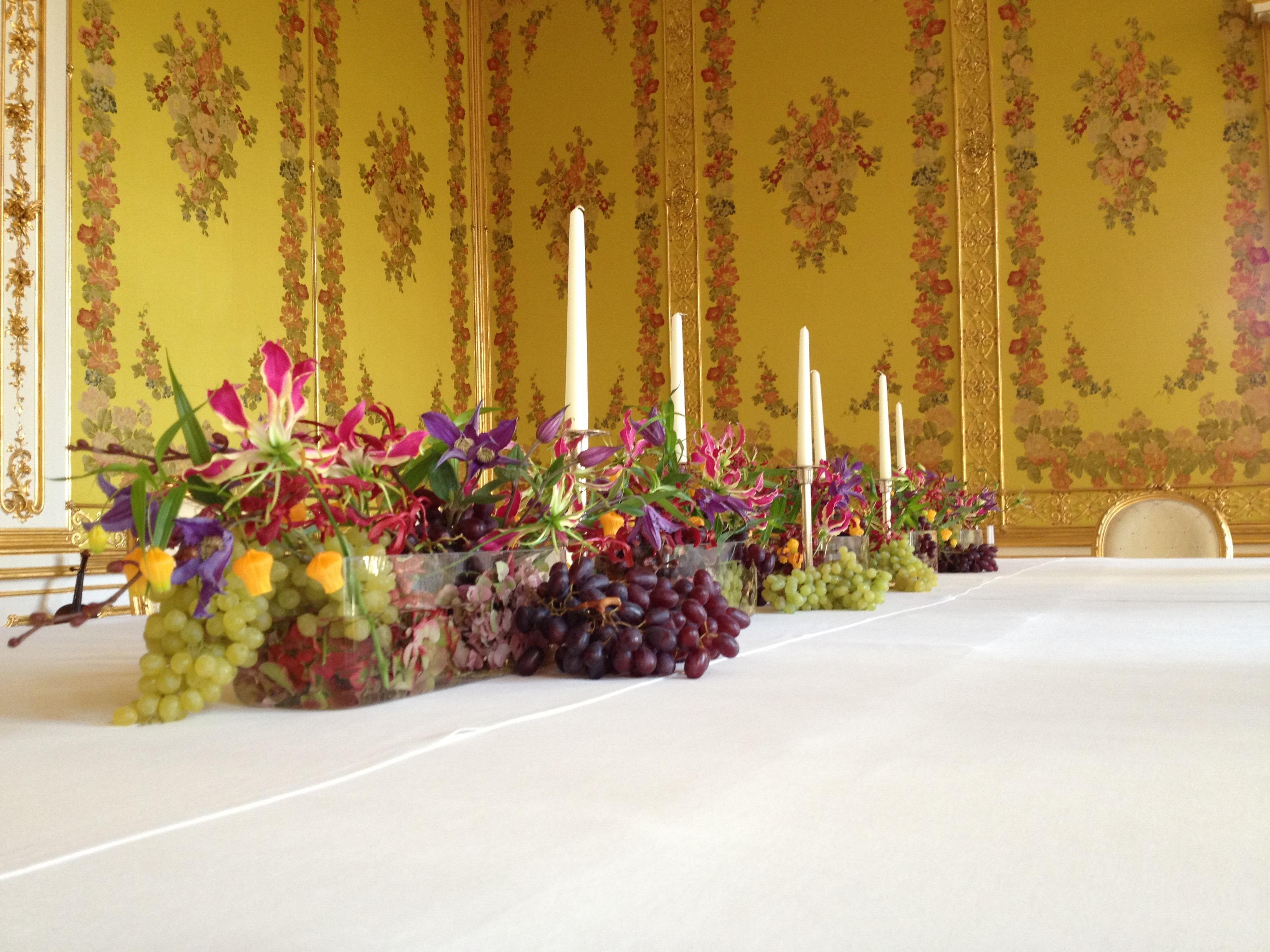 Hotelfloristik langes Arrangement mit bunten Blumen in langer durchsichtigen Glasschale mit roten und gruenen Weintrauben