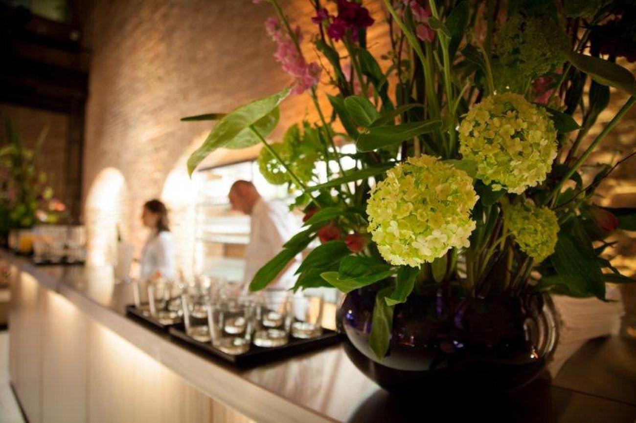 Hotel Florist breite Vase mit gelben runden Blumen und verschiedenen gruenen Blattelementen und rosa Blumen im Hintergrund eine Theke mit Glaeser