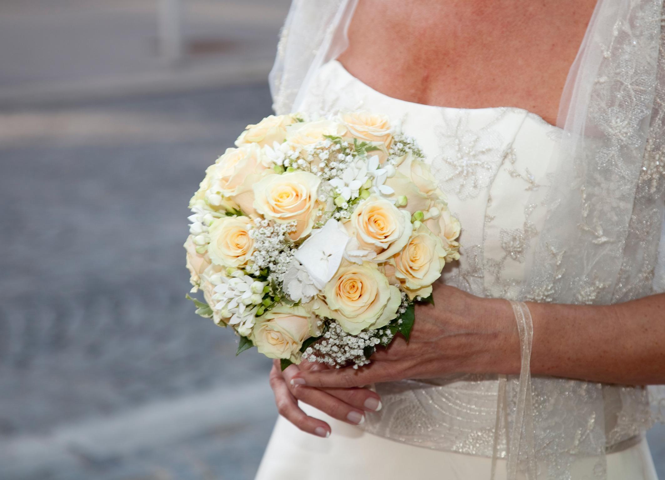 Hochzeitsfloristik Brautstrauss in gelb und weiss Toenen bestehend aus Rosen und kleineren weissen Blumen der von einer Braut im weissen Kleid das oebn bestickt ist gehalten wird