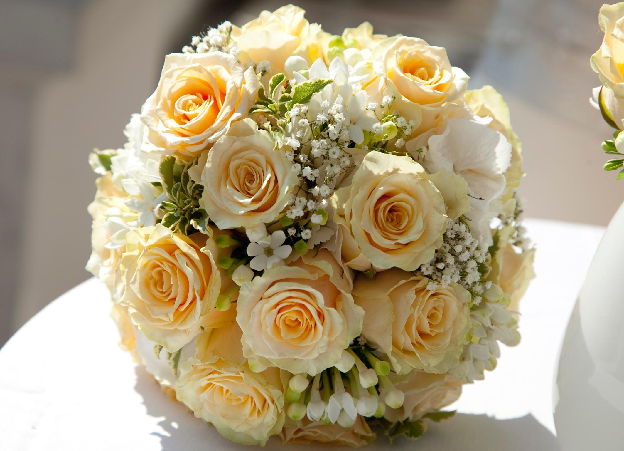 Hochzeitsfloristik Hochzeitsstrauss bestehend aus gelb orangen Rosen und kleineren weissen Blumen