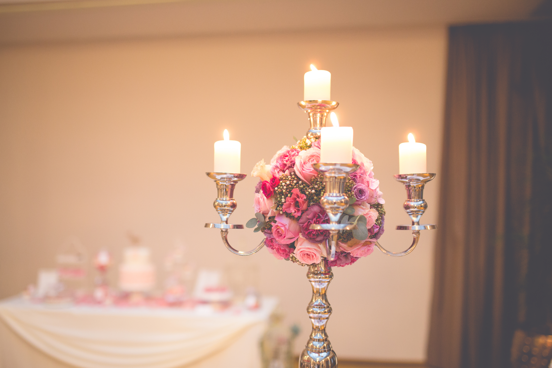 Hochzeitsfloristik Kerzenleuchter mit vier Kerzen und in der Mitte der Kerzen ein rundes Gesteck aus verschiedenen rosa Blumen hauptsaechlich Rosen