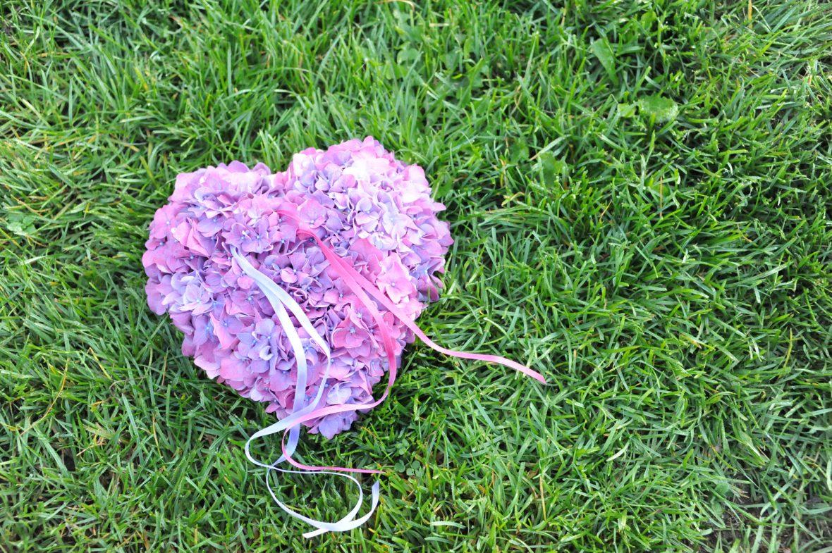 Hochzeitsfloristik Gesteck in der Form eines Herz aus kleinen rosa Blumen liegend in einer Wiese