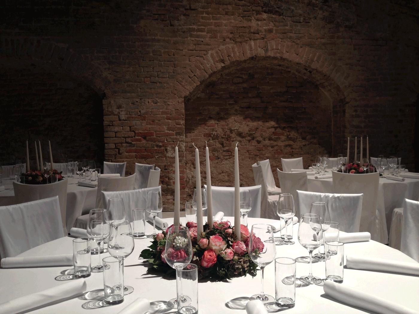 Event Floristik in einem Gewölbe mit schön gedecktem weißen Tisch und rosa Rosen Gesteck mit Kerzen auf dem Tisch