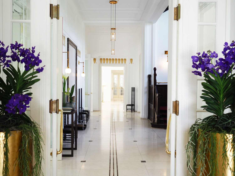 Hotelfloristik edler wiesser Gang mit Fliesen auf der Seite lila hohe Blumen die aus einem goldenen hohen Topf herauswachsen mit gruenen Blattelementen
