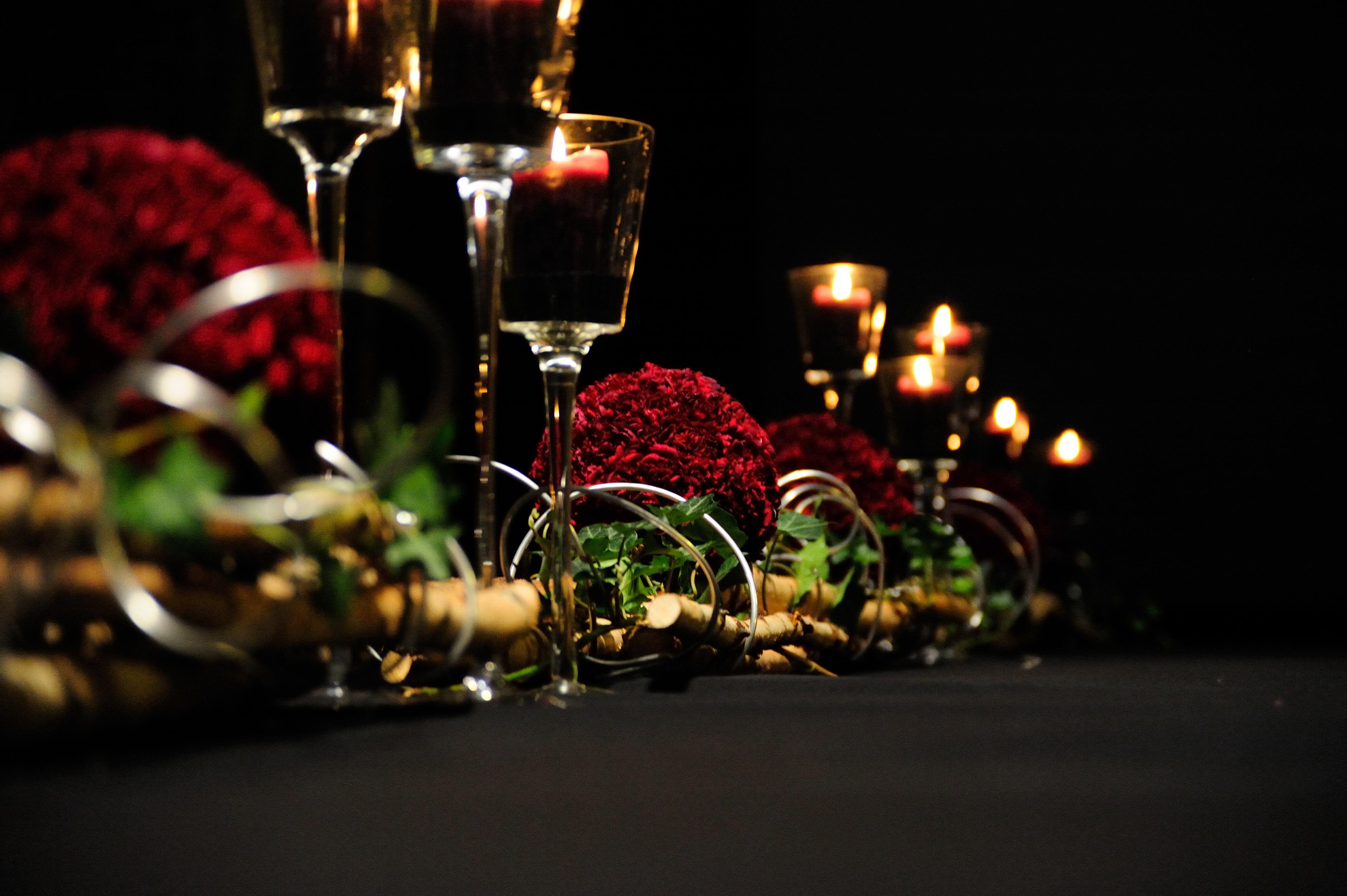 Eventfloristik langer Tisch mit schwarzem Tischtuch mit roten runden Blumengestecken die auf Bambusstangen und gruenen Blaettern liegen Kerzenleuchter am Tisch