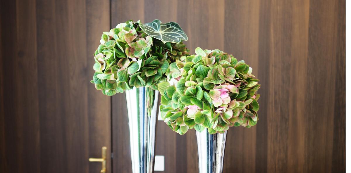 Hotelfloristik Blumen in silber Topf in den Farben gruen und rosa im Hintergrund dunkles Holz