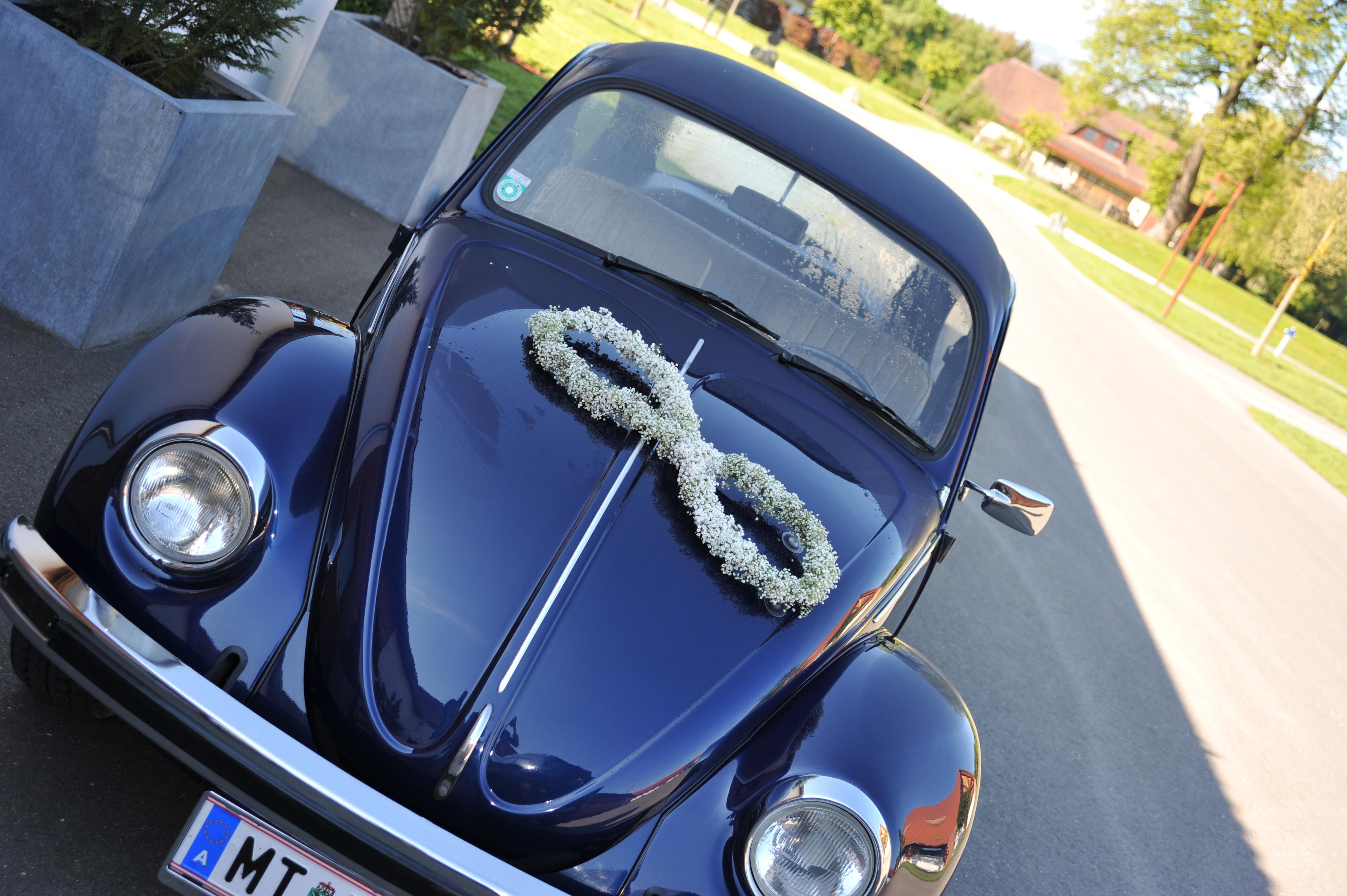 Hochzeitsflorist Brautauto schwarzer Kaefer mit Gesteck aus weissen Blumen in der Form des Unendlichkeitszeichen