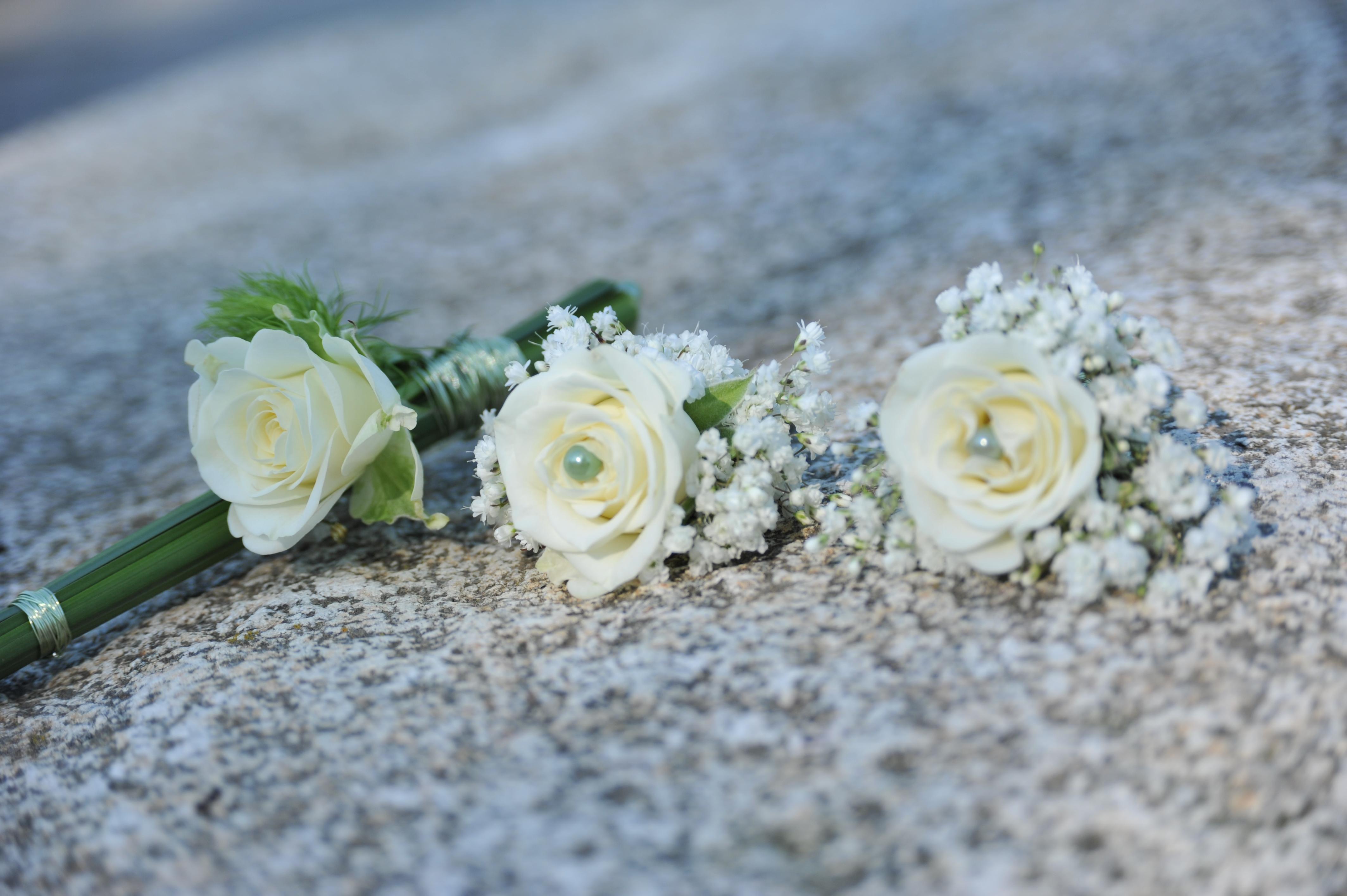 Hochzeitsfloristik Anstecker aus weissen Rosen und kleinen weissen Blumen zusammengebunden