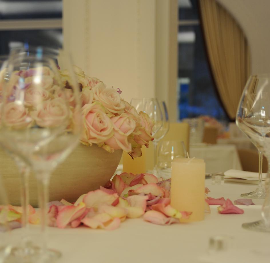 Hochzeitsfloristik Schale mit rosa Rosen und Rosenblaetter auf dem Tisch mit weissem Tischtuch und Kerzen