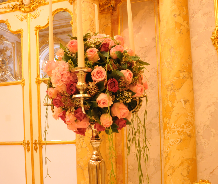 Hochzeitsfloristik Kerzenleuchter mit vier Kerzen und in der Mitte der Kerzen ein rundes Gesteck aus verschiedenen rosa Blumen hauptsaechlich Rosen und gruenen Elementen
