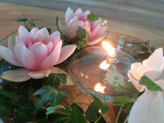 Hochzeitsfloristik Seerosen schwimmend mit Efeu in einer durchsichtigen Schale mit durchsichtiger Kerze in der Mitte
