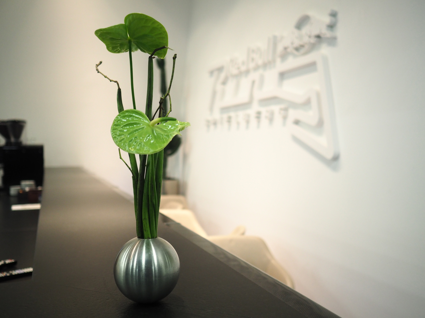 Firmenfloristik zeitlose gruene Blumee in kleiner runden silbernen Vase im Firmengebaude