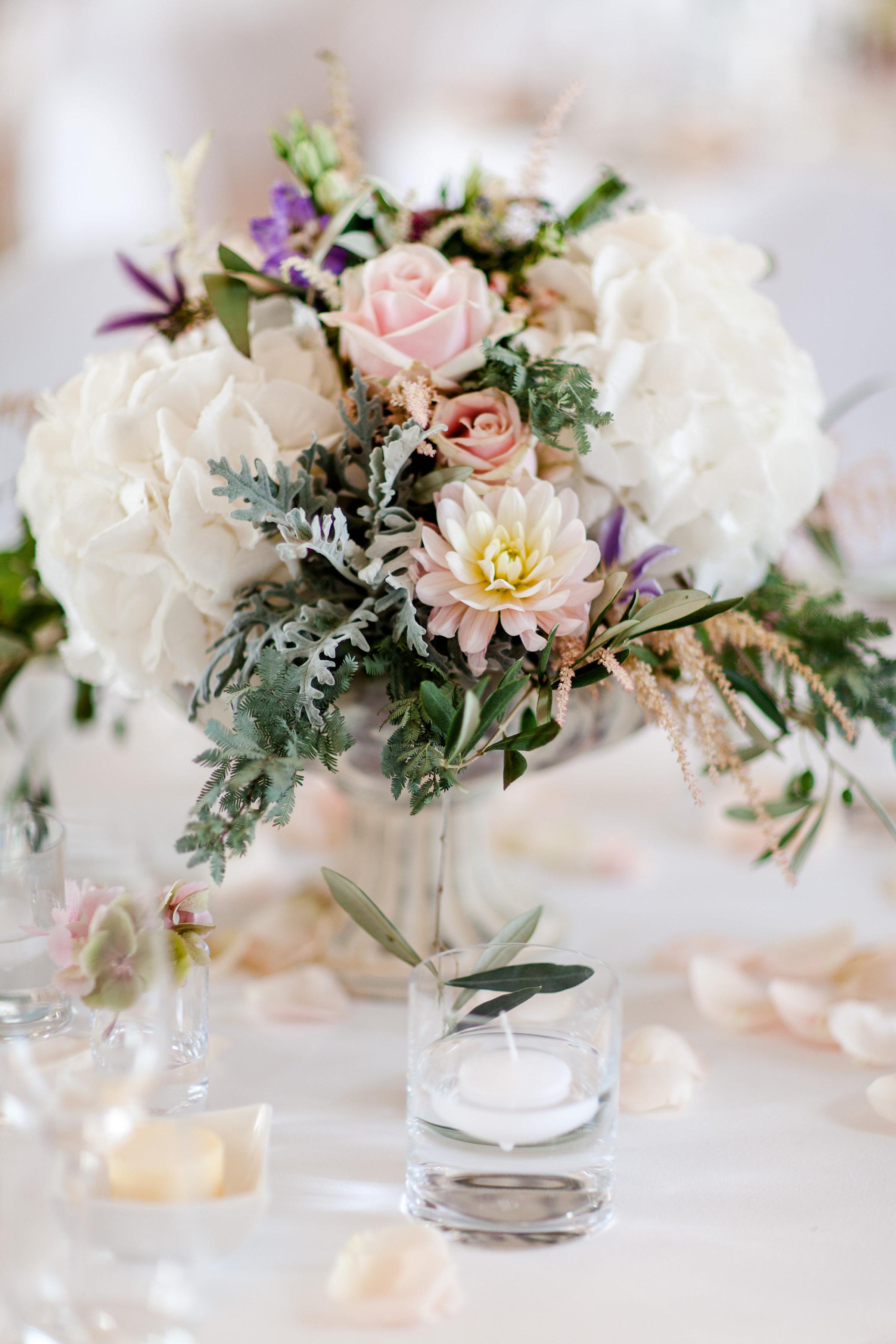 Hochzeitsfloristik Gesteck aus verschiedenen frischen Farben wie rosa violett weiss und geld mit verschiedenen Blumen mit gruenen Blaettern auf Tisch mit Kerze stehend