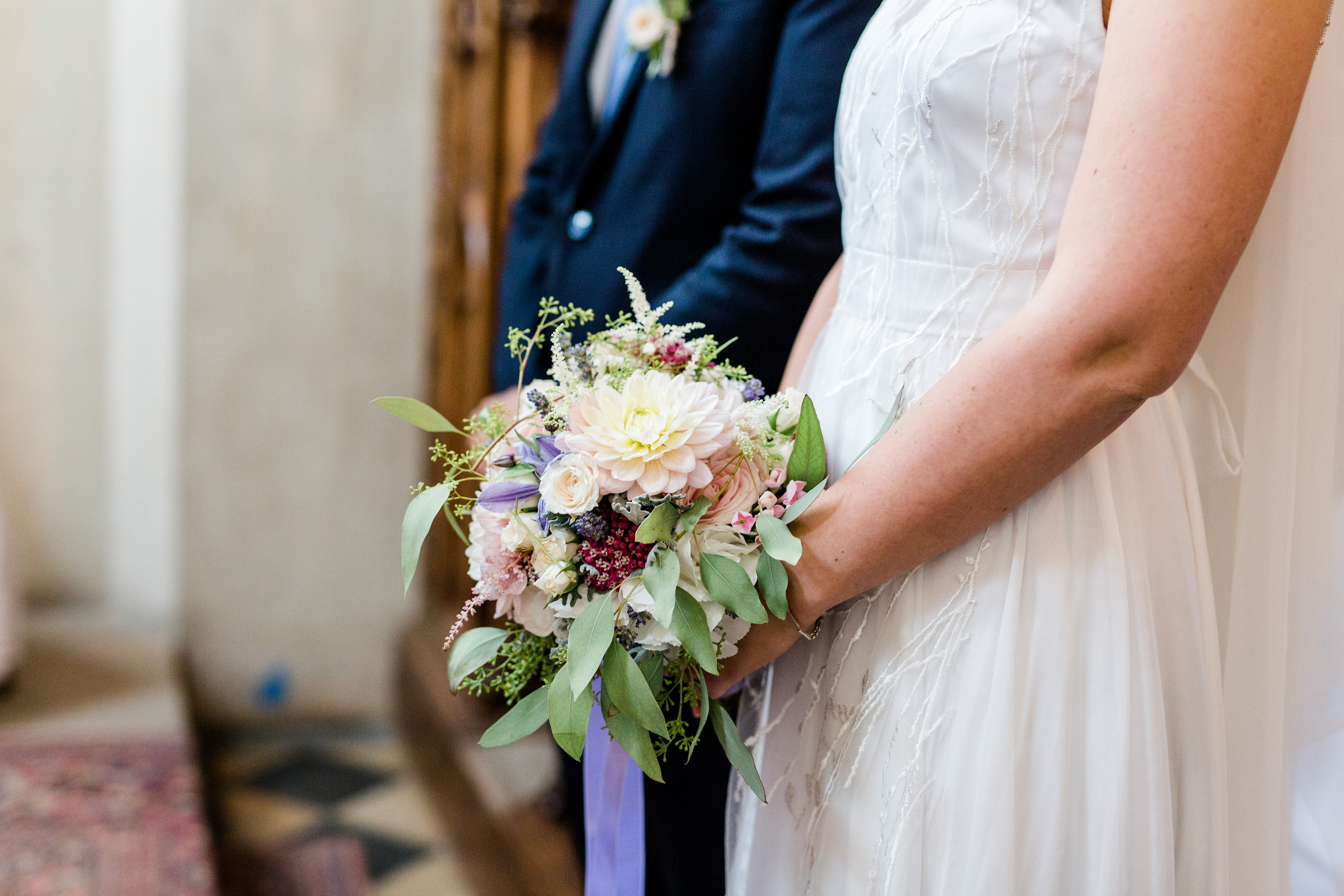 Hochzeitsfloristik Brautstrauss in rosa violett und weiss Toenen bestehend aus verschiedenen Blumen der von einer Braut im weissen Kleid das oebn bestickt ist gehalten wird und Braeutigam steht nebenan