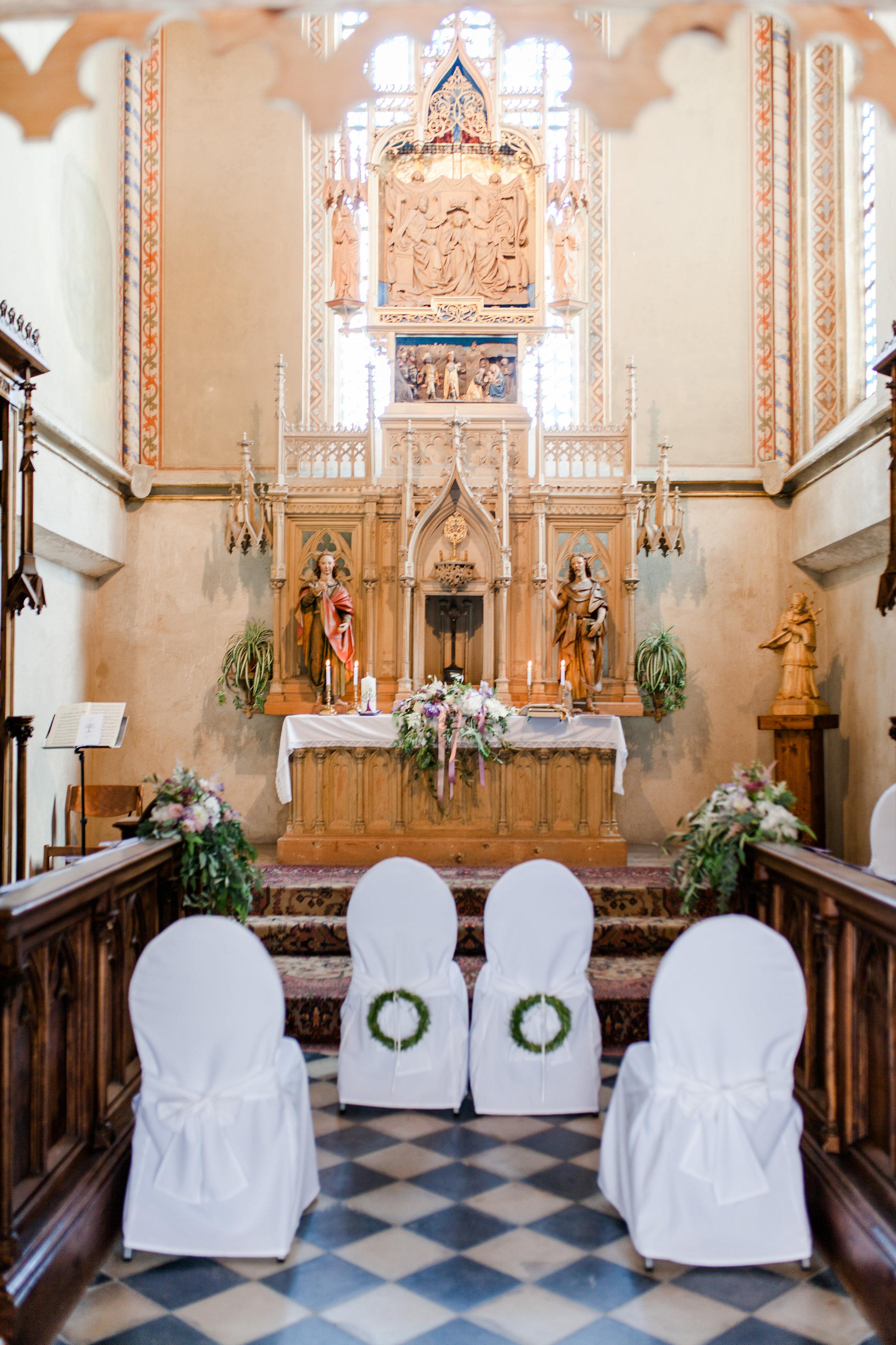 Hochzeit Kriche grosser Altar geschmueckt mit Gestecken die hautsaechlich gruen sind mit rosa und weissen Blumen und in der Mitte weisse Sessel mit gruenem Kranz an der Lehne befestigt