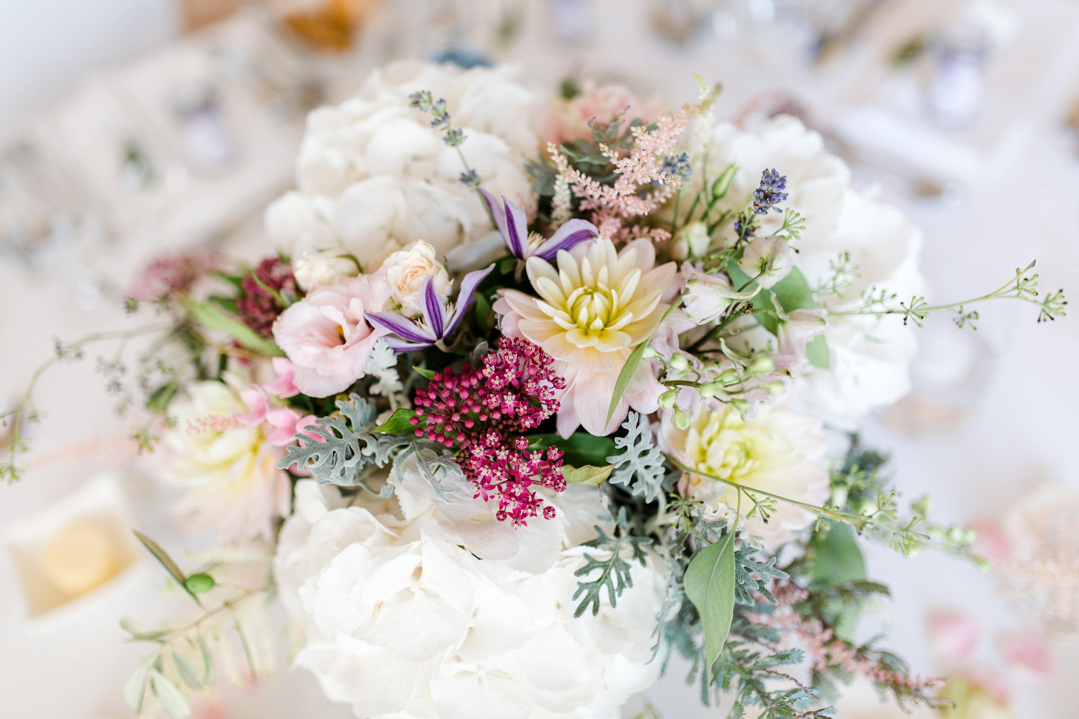 Hochzeitsfloristik Gesteck aus verschiedenen frischen Farben wie rosa violett weiss und geld mit verschiedenen Blumen mit gruenen Blaettern