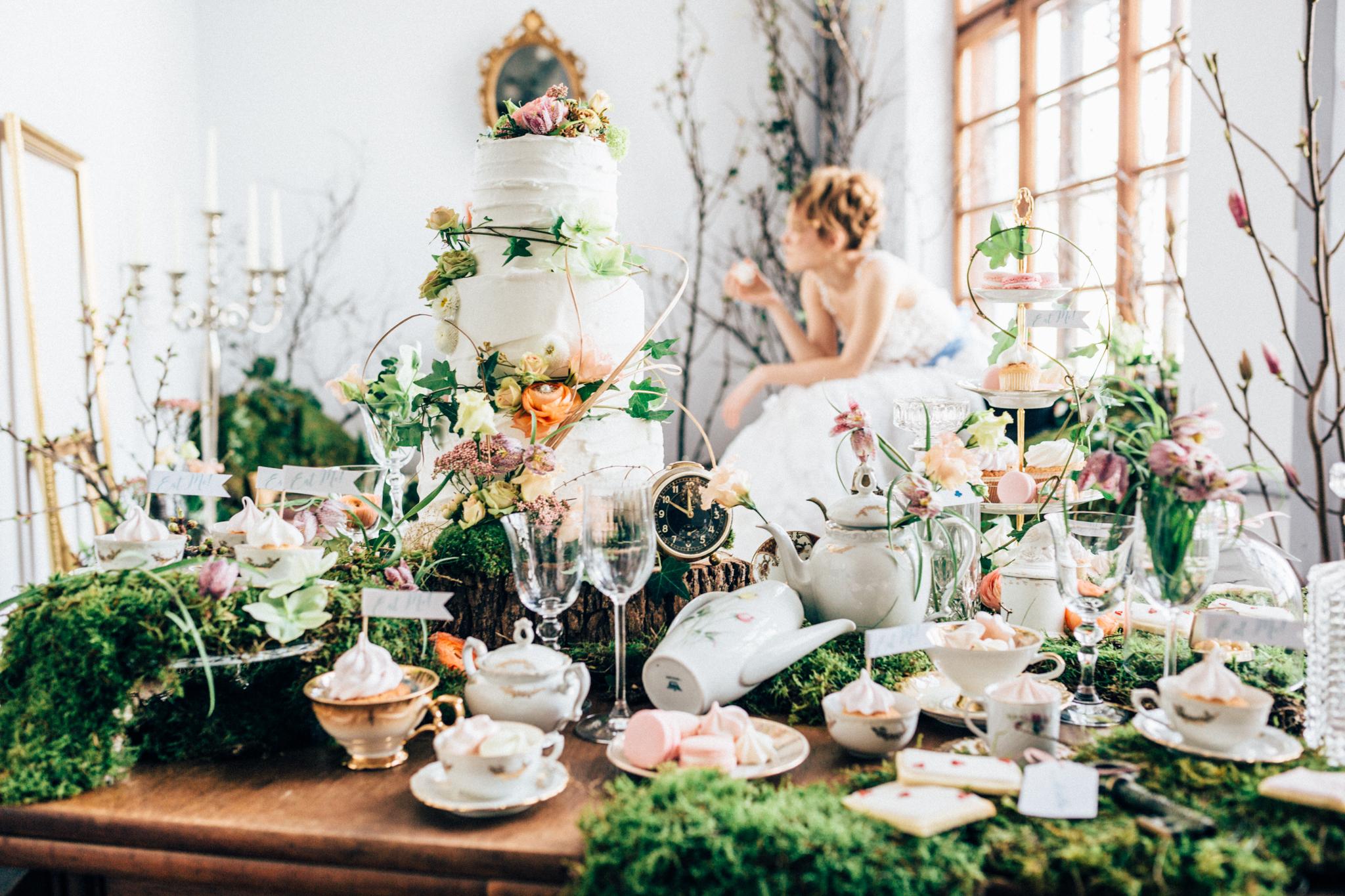 Hochzeitsfloristik Tisch mit vielen Arrangements Moos und verschiedenen Blumen in orange und rosa weisse hohe Torte mit Blumen im Hintergrund eine essende Braut im weissen Kleid