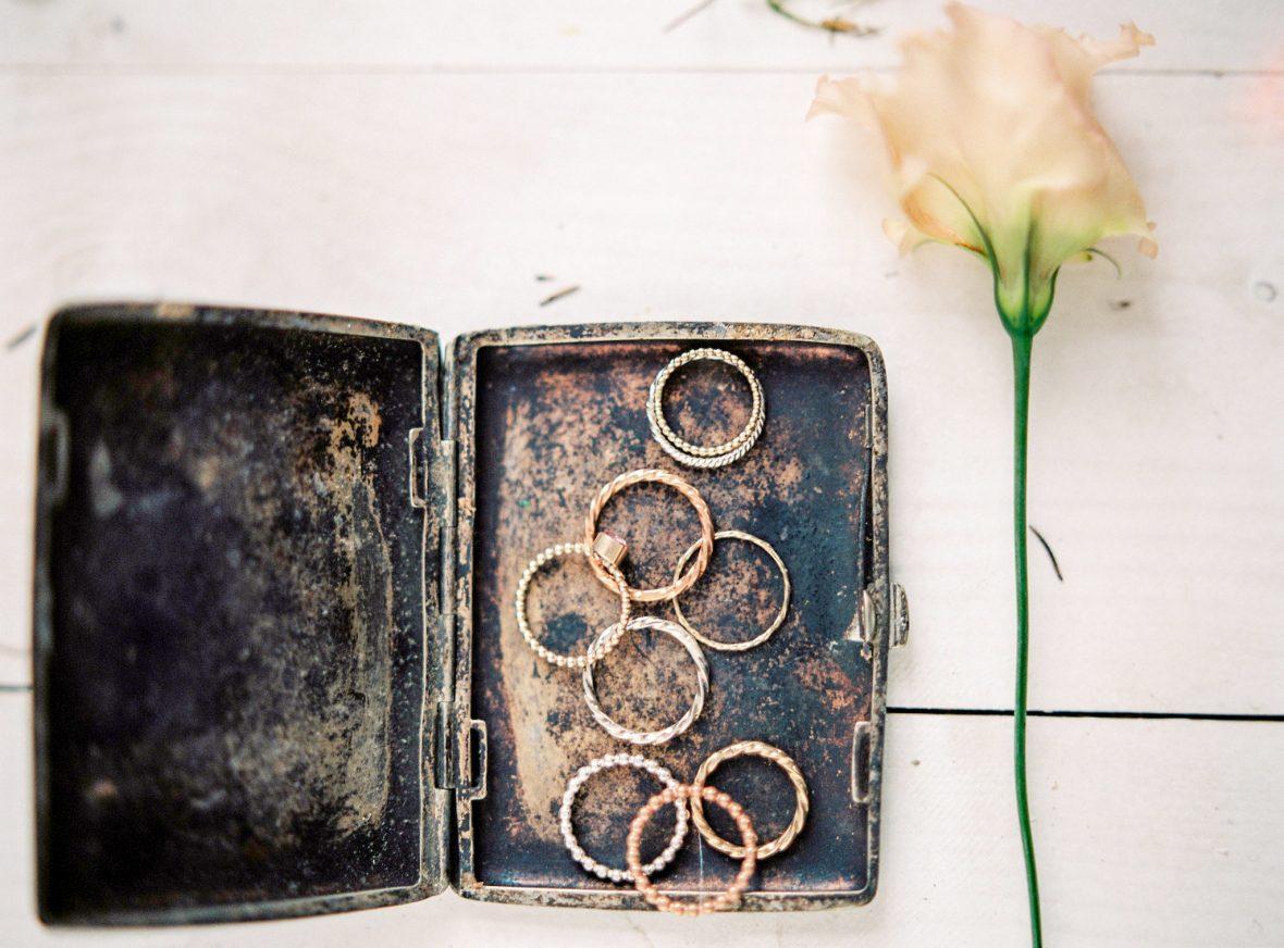 Hochzeitsfloristik aeltere Kiste mit vielen Ringen drinnen nebenbei einzelne weiss gelbe Rose