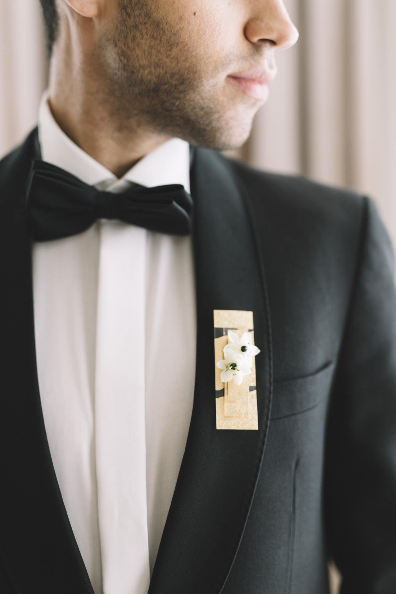 Hochzeitsfloristik Anstecker gold mit weisser Blume am Braeutigam