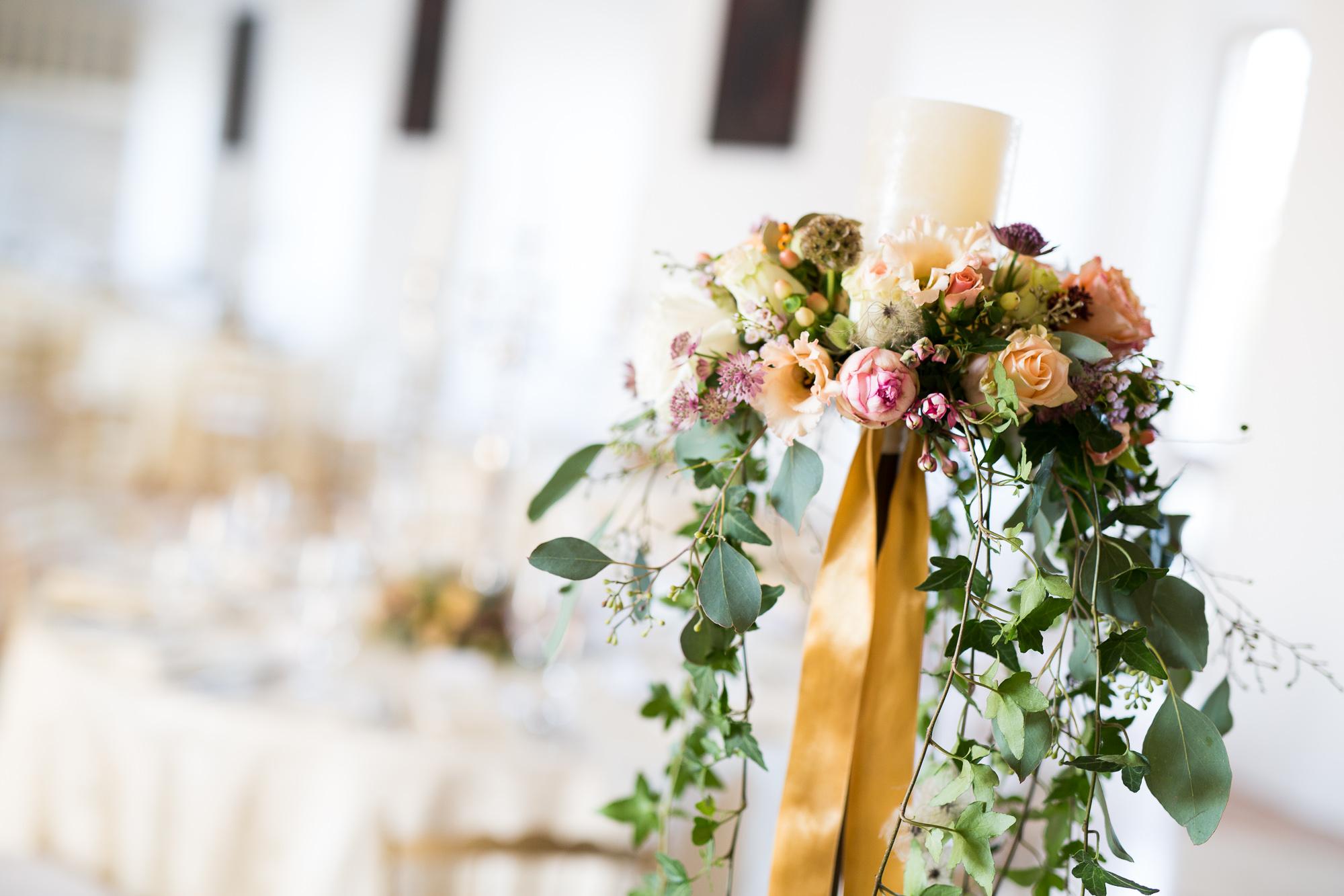 Hochzeitsfloristik Gesteck Kerzenstaender mit weisser Kerze und herum rosa orange und weisse Blumen mit runterhaengendem Efeu