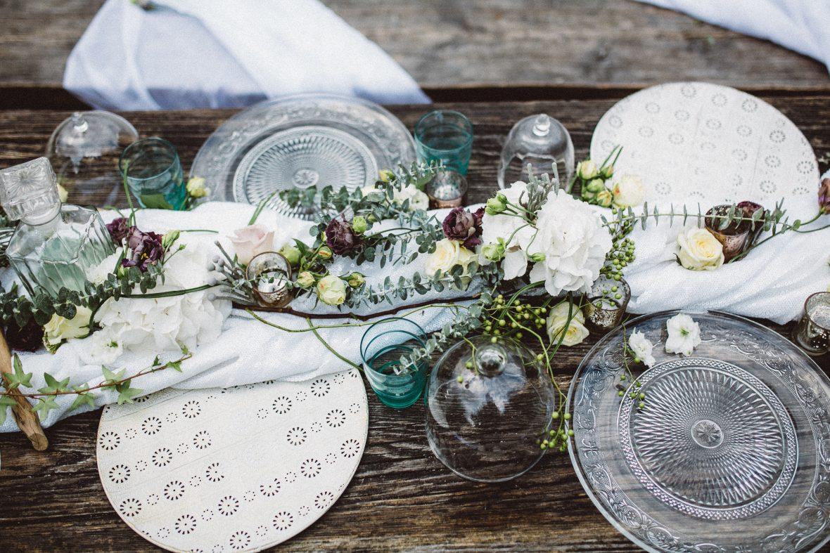Hochzeitsfloristik Gesteck am gedeckten Holztisch aus weissen grossen Blumen udn kleineren gelb weissen Rosen und dunkelvioletten Blumen mit Aesten auf weissen Tuch