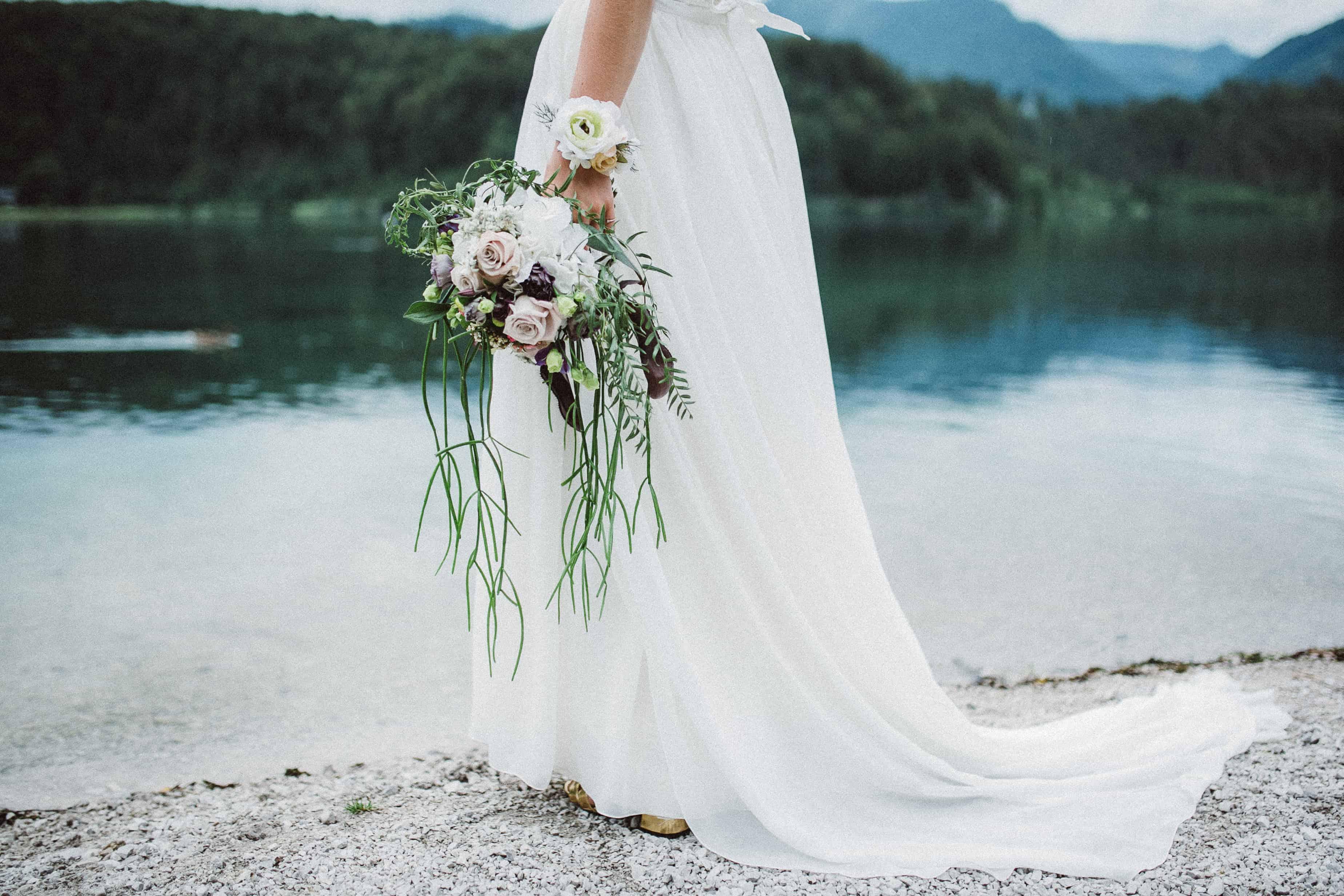 Hochzeitsfloristik Brautstrauss in hellviolett weiss und gruen mit Rosen und herunterhaengenden gruenen Pflanzen gehalten von einer Braut im weissen Kleid