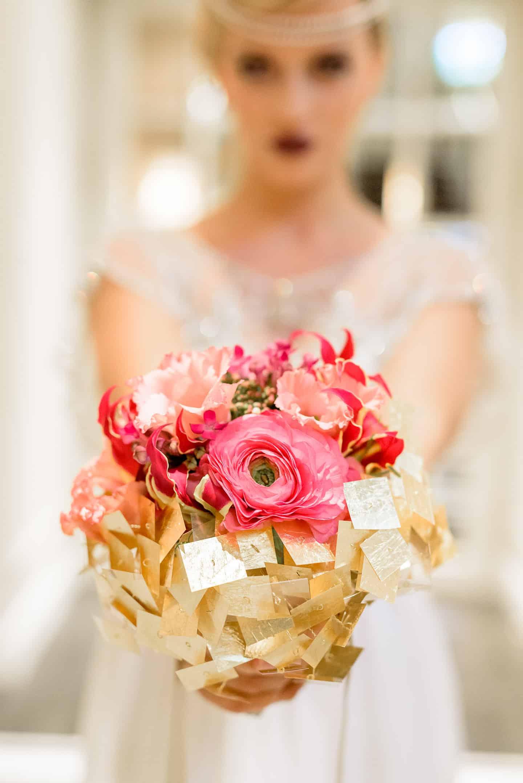 Hochzeitsfloristik Brautstruass mit rosa Blumen im Hintergrund Braut mit weissen Kleid