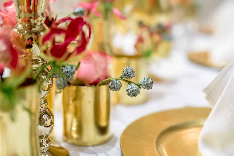 Hochzeitsfloristik gedeckter Tisch mit goldenen Geschirr und Glaesern mit roten Blumen