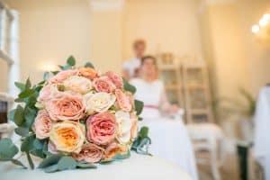 Hochzeitsfloristik Brautstrauss aus rosen in den Farben rosa gelb orange und weiss auf Tisch liegend un im Hintergrund Braut sitzend im weissen Kleid
