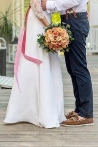 Hochzeitsfloristik Brautstrauss aus rosen in den Farben rosa gelb orange und weiss gehalten von der Braut und Braeutigam steht ihr gegenüber und nimmt sie in den Arm