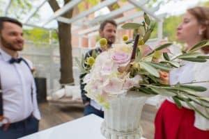 Hochzeitsfloristik Blumen in den Farben rosa gelb und gruene Blaetter in einer alten Steinvase auf einen Tisch stehend im Hitnergrund zwei Maenner und eine Frau die sich unterhalten